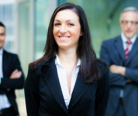 Business woman in foreground with two businessmen behind her